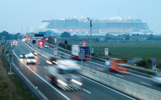 Berufsverkehr am Emstunnel, im Hintergrund das Kreuzfahrtschiff AIDAnova
